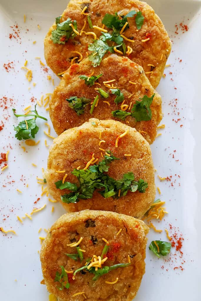 Close up image of crispy spicy potato cakes garnished with cilantro and sev.
