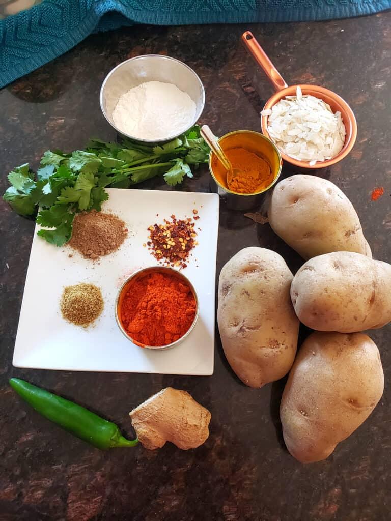ingredient needed to make masala potato patties displayed on black countertop.