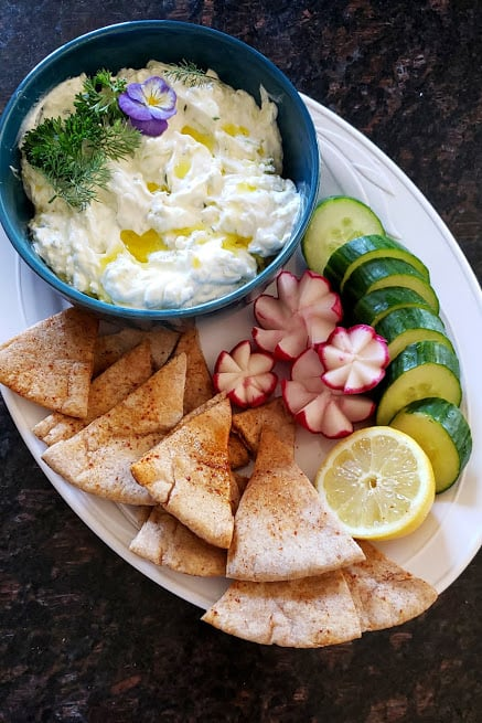 Greek Tzatziki sauce garnished with olive oil and fresh dill served with pita chips and cucumbers served as mezze platter.