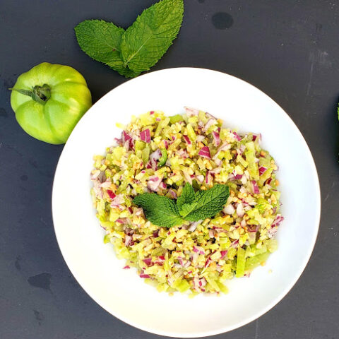A salad plate full of green tomatoes and red onions and crushed peanuts mixed together to make refreshing garden fresh salad. This salad is full of garden fresh vegetables.