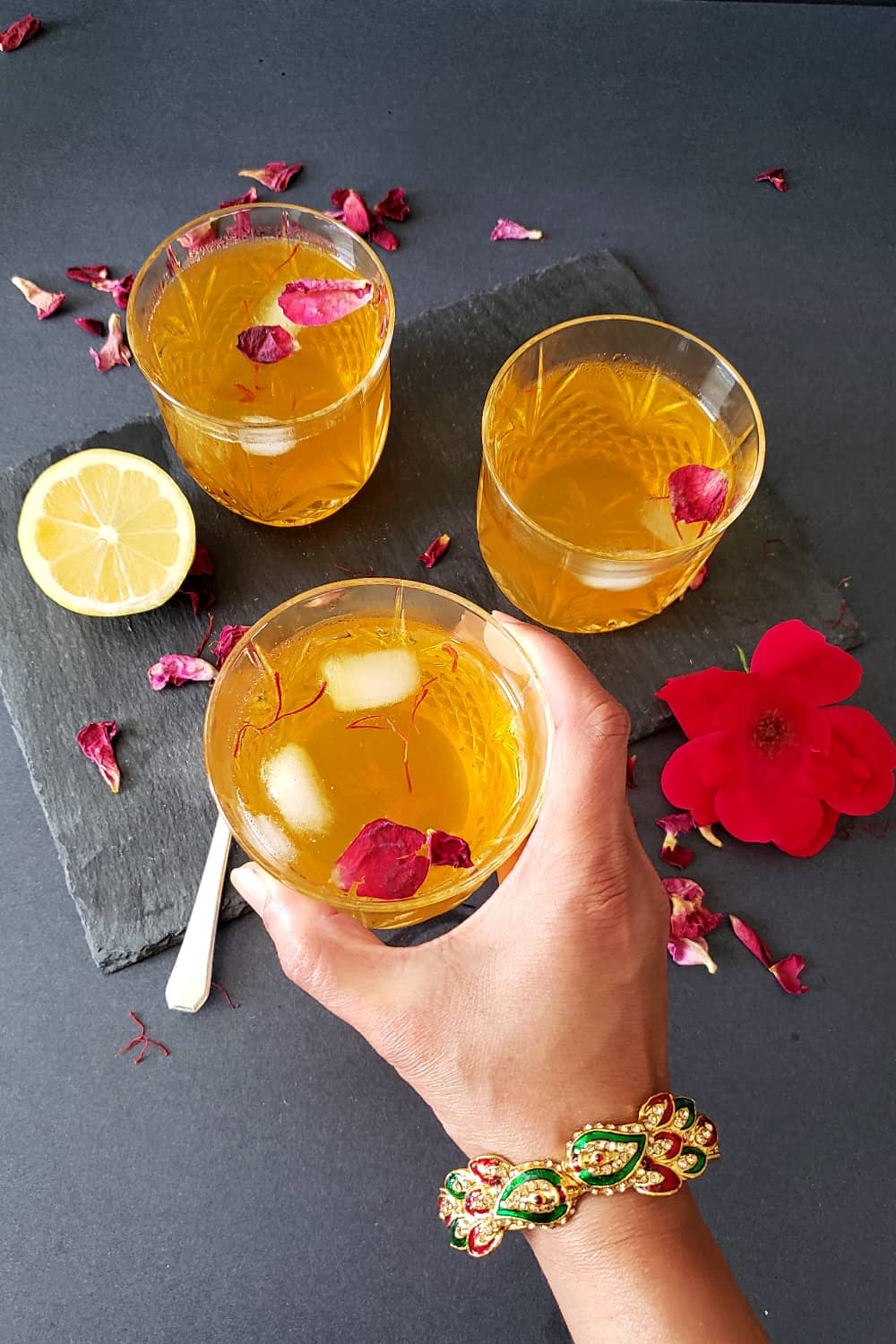 A hand holding glass of chilled saffron rose lemonade