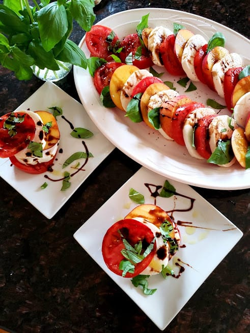 A white salad serving platter and two salad plates full of tomamto peach caprese salad.