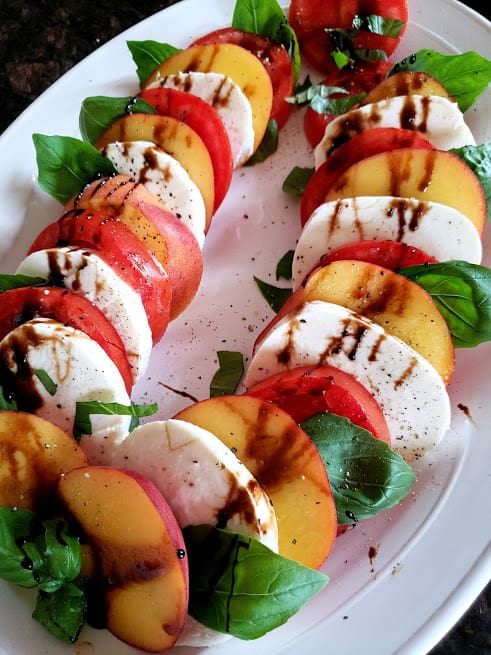 Layered peach and tomato salad generously drizzled with balsamic vinegar glaze.
