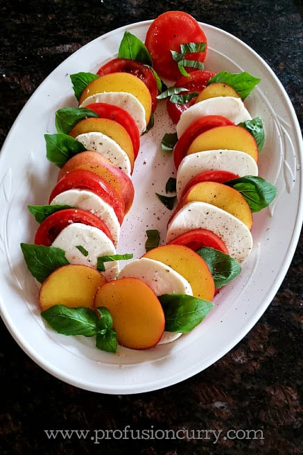 Layers of peach, tomato, basil and cheese slices arranged on salad platter.