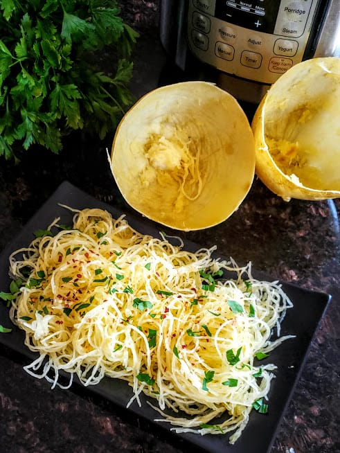 A dinner plate full of seasoned spaghetti squash noodles cooked in electric pressure cooker Instantpot.