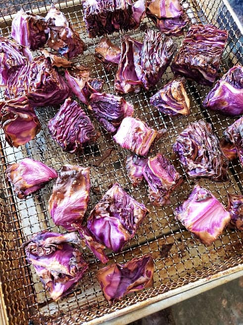 Nicely charred red cabbage steaks on airfryer basket.