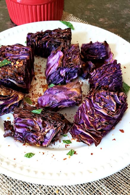 A close up image showing beautiful and crisp layers of red cabbage steaks airfried and seasoned with herbs.