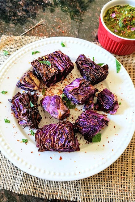 Bunch of air fried red cabbage steaks garnished with red pepper flakes and herbs served on a white dinner plate. A bowl full of chimichurri sauce is in the background for dipping.