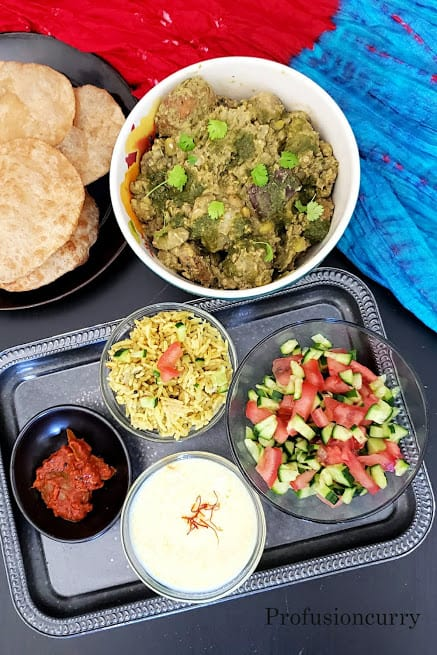 A bowl of undhiyu, with 5 puries and a metal tray full of condiments.