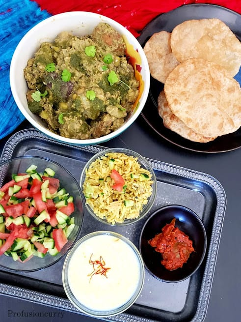 A traditional dinner serving with puffed puries, undhio, sweet rice kheer, pickle, salad and marmara.