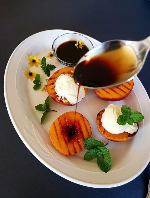 A pour shot of maple balsamic glaze over grilled peach.
