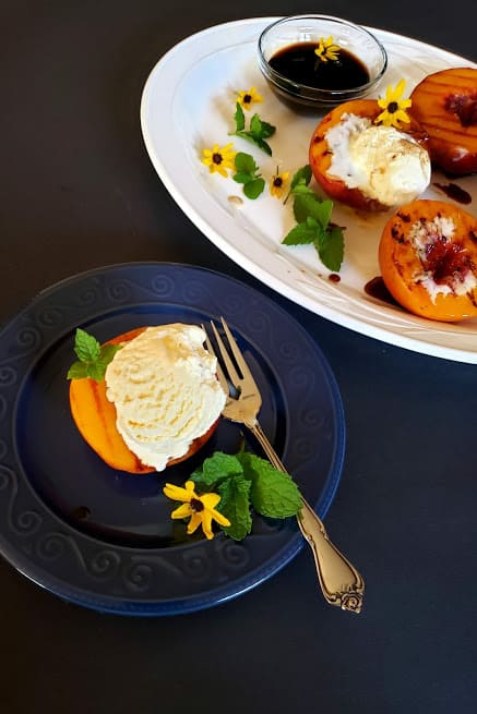 Grilled peaches served with vanilla nice cream in blue dessert plate.