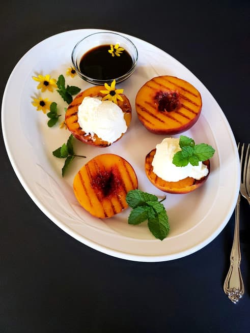 grilled peaches topped with dollop of ice cream garnished with mint and edible flowers.