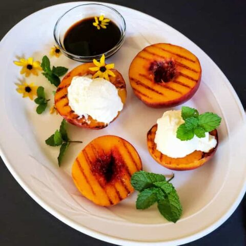 A white serving platter full of grilled peaches, a bowl of balsamic glaze , mint leaves and ice cream.
