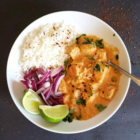 A dinner plate with thai massman curry with vegetables, white rice, red onions and lime wedges.
