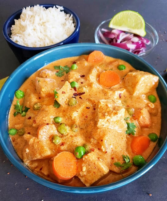 A close up showing luxuriously creamy yellow coconut curry with peas, carrots and potatoes.