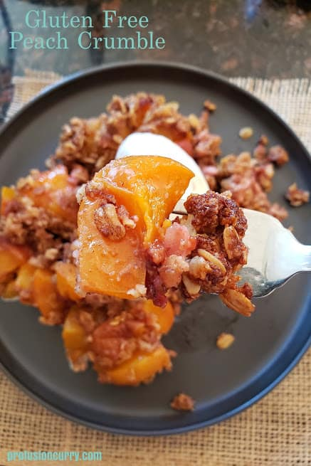 Close up image of fork holding cooked peach and granola.