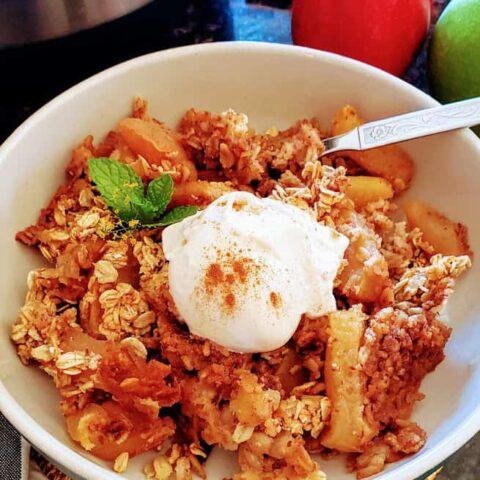 Close up image of apple crisp served with vanilla ice cream and ground cinnamon dusting