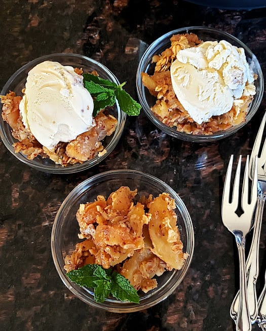 Apple Crisp dessert served in three small dessert bowls with coconut cream and ice cream dusted with cinnamon powder.