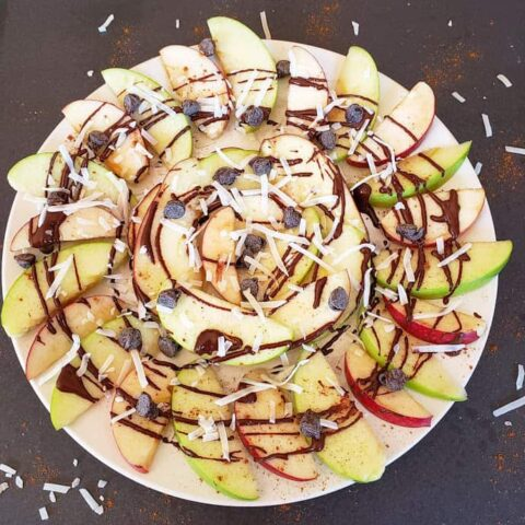 A white platter full of apple slices drizzled with chocolate sauce, chocolate chips, ground cinnamon and coconut flakes. This apple nacho recipe is easy to prepare and tastes amazing.
