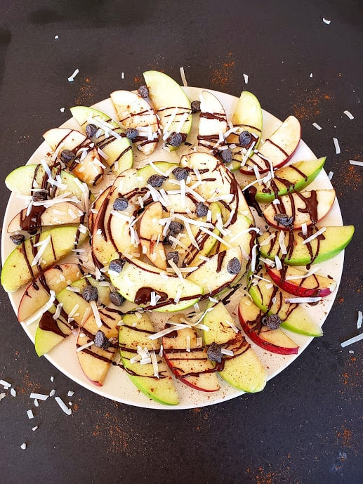 A white serving platter full of apple choclate nachos.