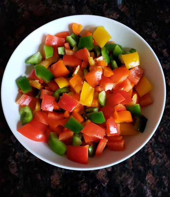 A bowl of colorful bell peppers cut into bite size pieces.