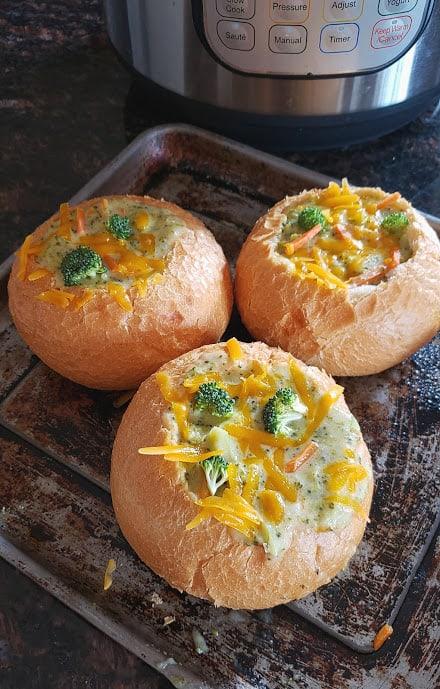 Three bread bowls filled with creamy broccoli cheddar soup.