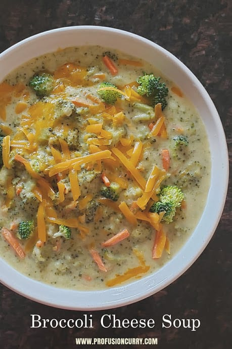 An overhead shot of white serving bowl filled with creamy soup and garnished with cheddar cheese.