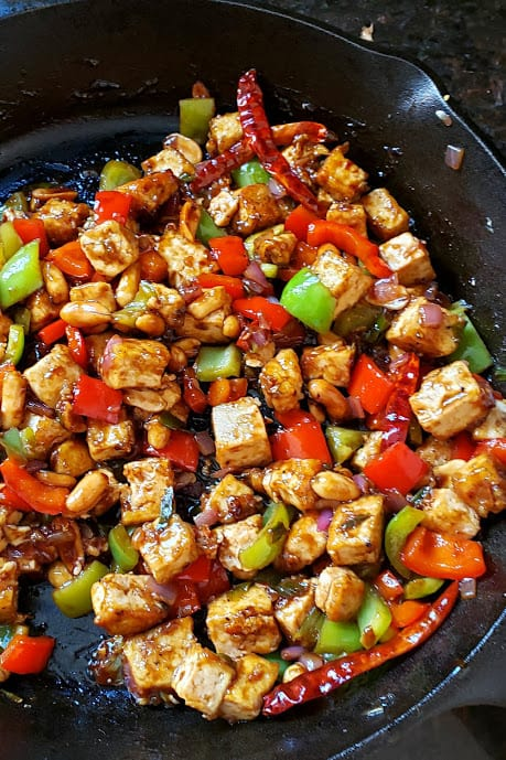 A cast iron skilett with colorful veggies and crispy tofu.