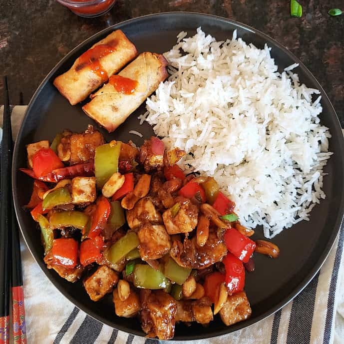 A black round plate with kung pao tofu, white rice and two spring rolls. A chopstick is on the side and dinner napkin under the plate.