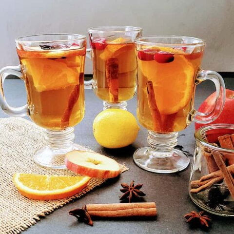 Spiced Apple cider filled glasses served with cinnamon, star anis and cloves.