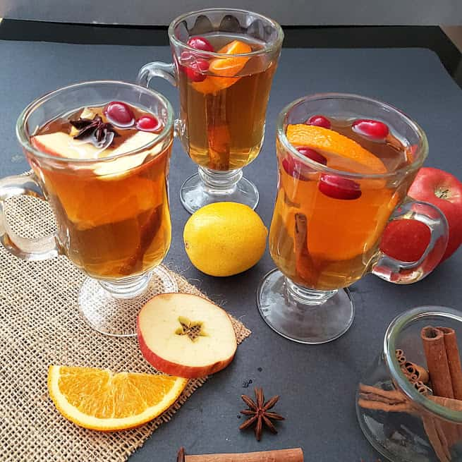Warm apple cider served with apple and orange wedges and cinnamon sticks in three beverage glasses.
