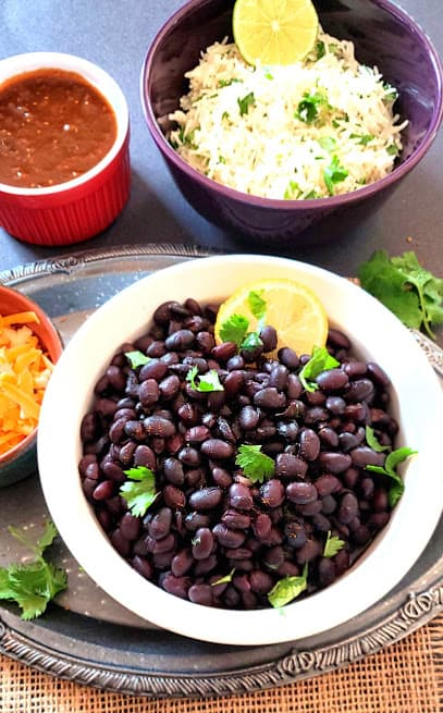 A dinner serving with bowls of black beans, salsa, cheese and cilantro lime rice.