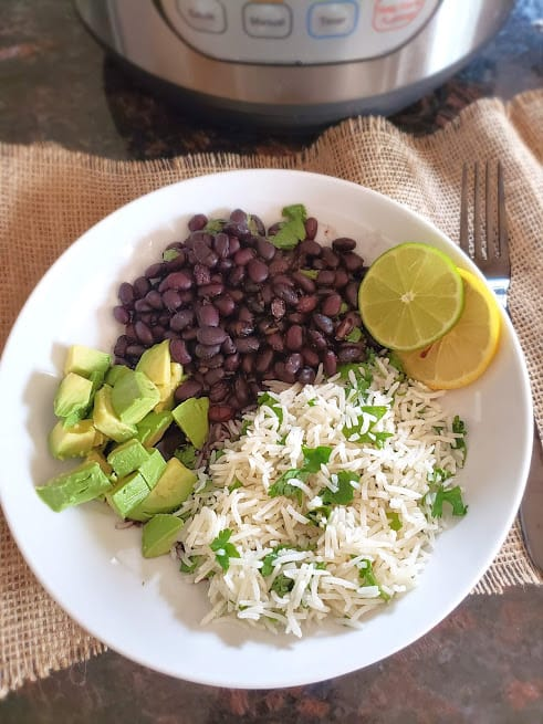 Cuban style seasoned black beans served with cilantro lime rice and avocado.