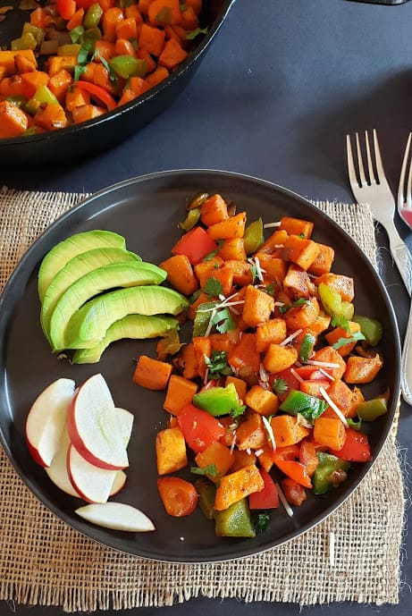 A black serving plate with stir fried sweet potatoes, bell peppers and seasoning served along with avocado and apple slices.
