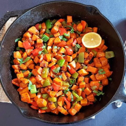 A skillet full of savory sweet potatoes and bell pepper hash.