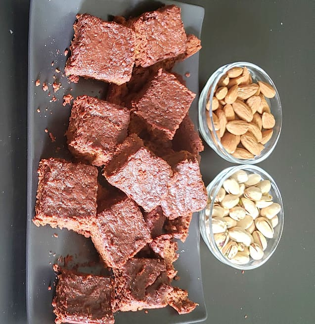 Cut brownie pieces served along with two bowls of almod and pistchoes served on black serving platter.