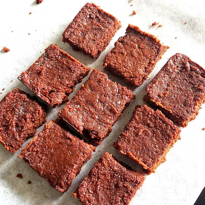 Chocolate Sweet Potato Brownies cut into pieces served on parchement paper.
