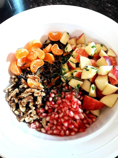 cooked wild rice, fruits and nuts ready to be tossed together.