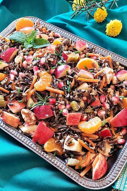 Wild Rice along with fruits, nuts and herbs served on decorative plate at a holiday dinner.