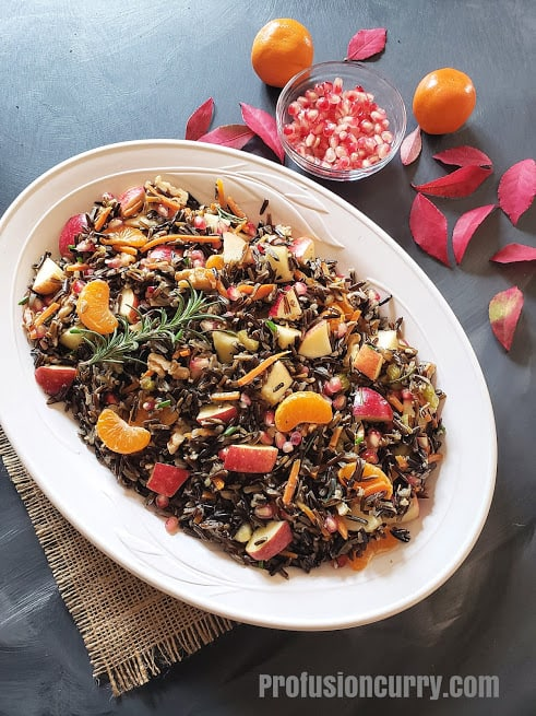 A white serving platter with wild rice stuffing along with fall foliage and oranges.