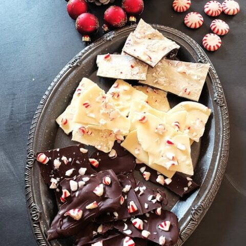 An assortment of dark, white and layered chocolate bark along with Christmas decorations.