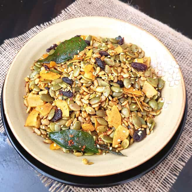 A serving plate full of Pumpkin seeds savory trail mix. It is spicy, sweet and salty mix full of superfood ingredients.