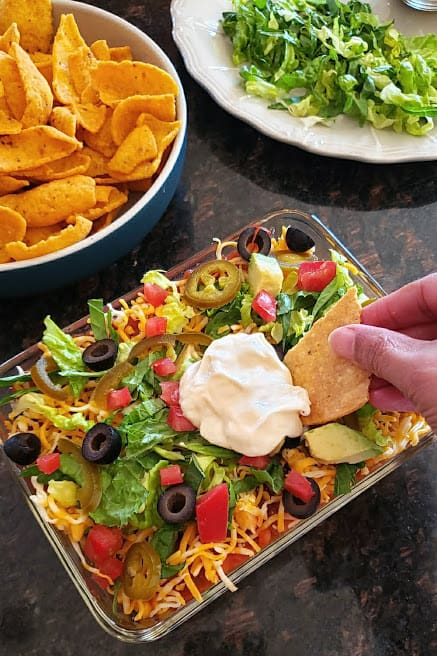 A hand holding a tortilla chip getting a scoop out of mexicn layered dip.