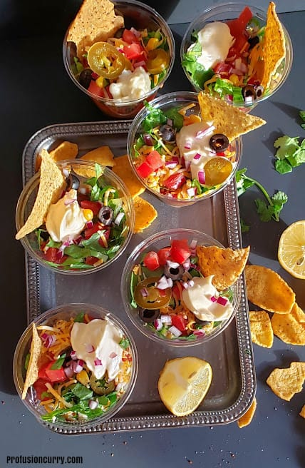 Overhead image of 6 cups full of layred mexican taco dip served on a vintage metal tray.