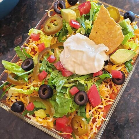 An overhead image of colorful 7 layer dip served in glass container. SHowing the delicious layers of olives, cheese, jalapeno, tomato, lettuce and sour cream with a tortilla chip dipped into this favorite party dip.
