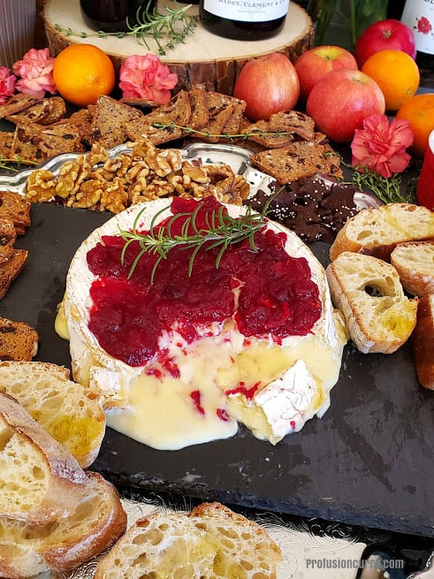 A festive party appetizer platter with wine and cheese.