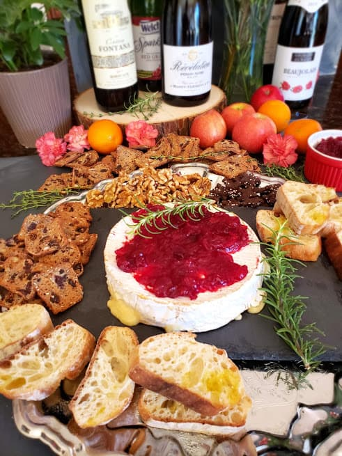 Baked Brie cheese topped with cranberry sauce and rosemary sprig served on a cheese board aong with other accompaniments.