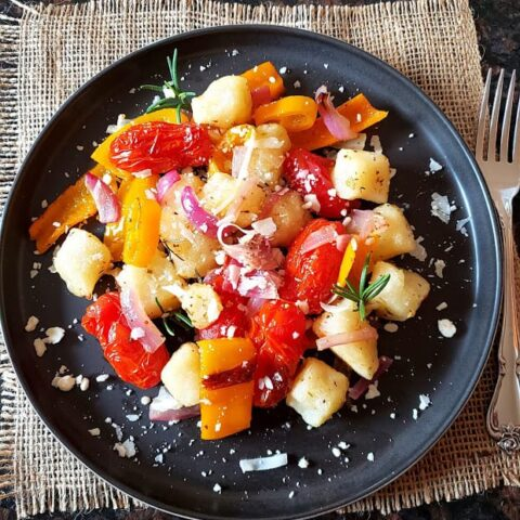 Cauliflower Gnocchi and rainbow veggies sheet pan dinner served on the dinner plate.