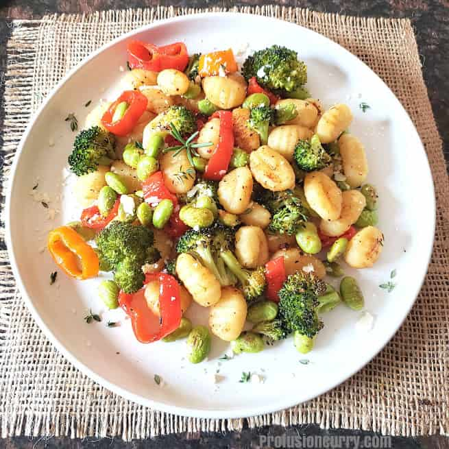 Vegan gnocchi and colorful vegetables baked in the sheet pan and served for dinner.
